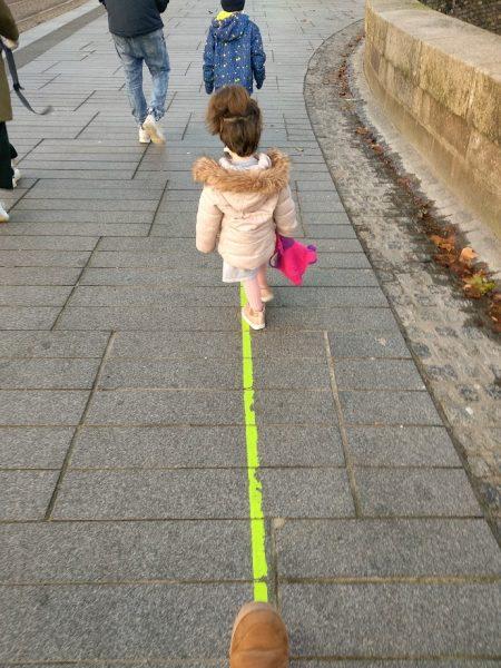 niños en fila siguiendo la linea verde