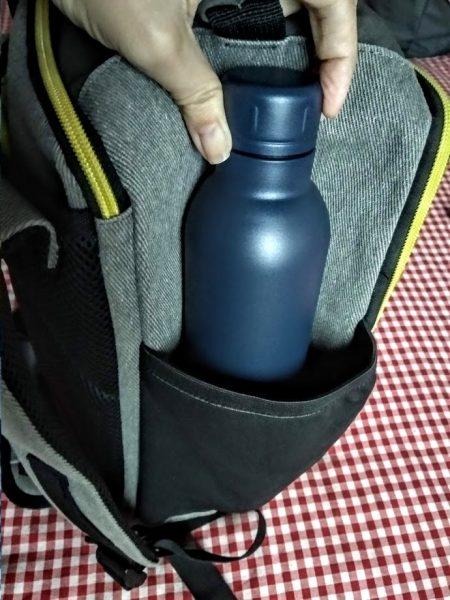 Botella termo azul en bolsillo lateral de la mochila de mano