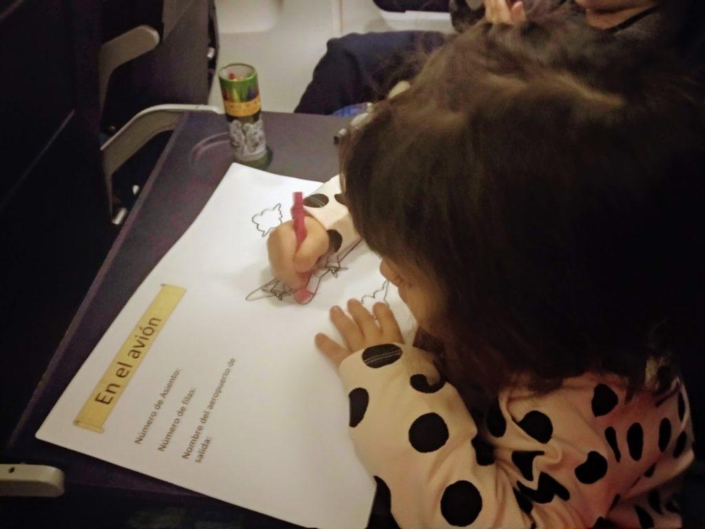 Niña coloreando pasaporte en la mesa auxiliar del avión