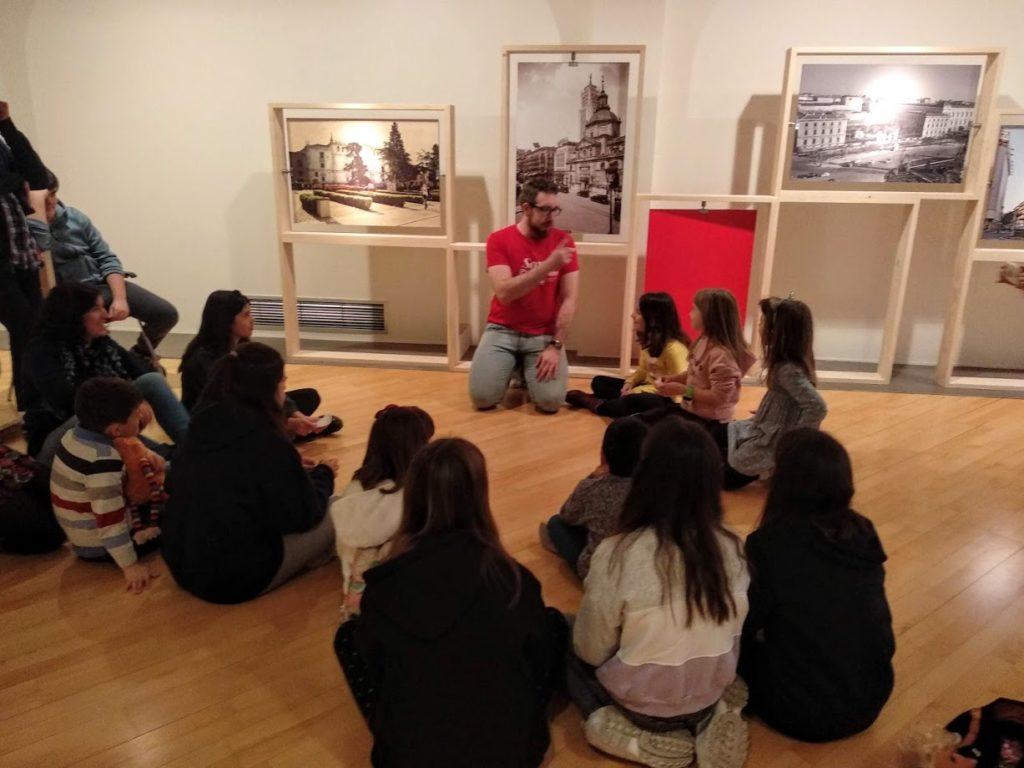 Grupo de niños alrededor del monitor. Detrás fotografías antiguas en paneles