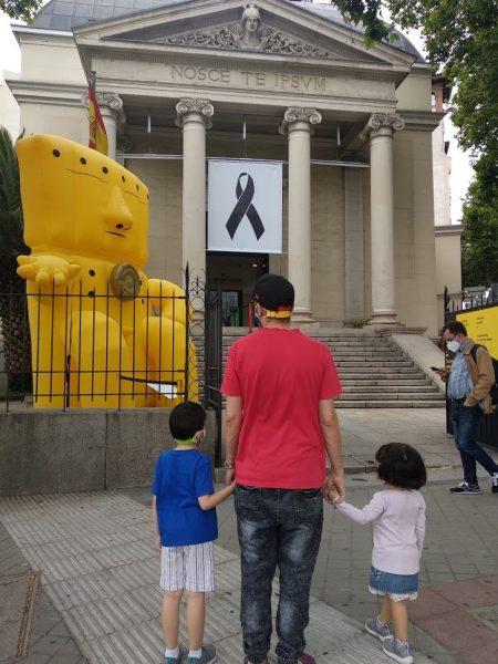 Entrada al museo, de espaldas el padre con los dos niños de la mano.