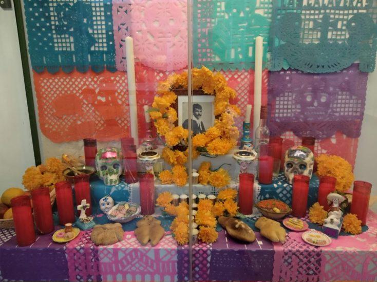Altar colorido de muertos estilo mexicano, con la foto del difunto, velas, comidas favoritas...