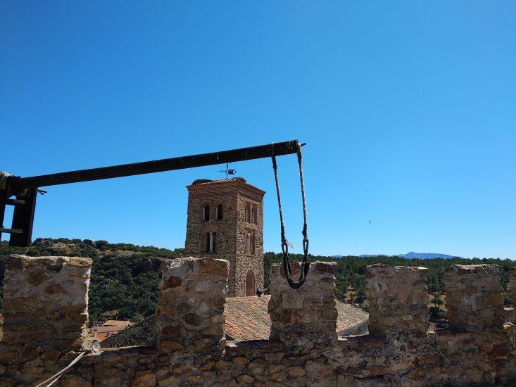 Foto desde la muralla, en un lado una de las lanzaderas medievales y al fondo torre de la iglesia
