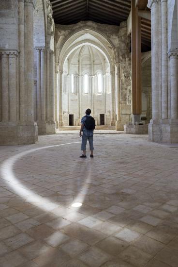 Persona en el interior del templo, al fonodo una de las capillas con arcos ojivales.