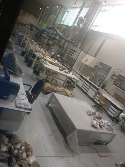 Territorio dinópolis mesas y demás del laboratorio de paleontología, uno de ellos trabajando