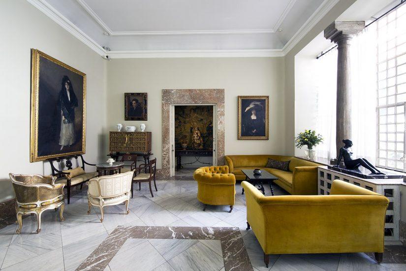 Imagen del salón de la casa con varios sofás y esculturas, cuadros y un secreter