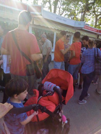 En la feria del libro con el carrito de bebe de la peque y el hermano subido en el patín del carrito, muy pequeños los dos